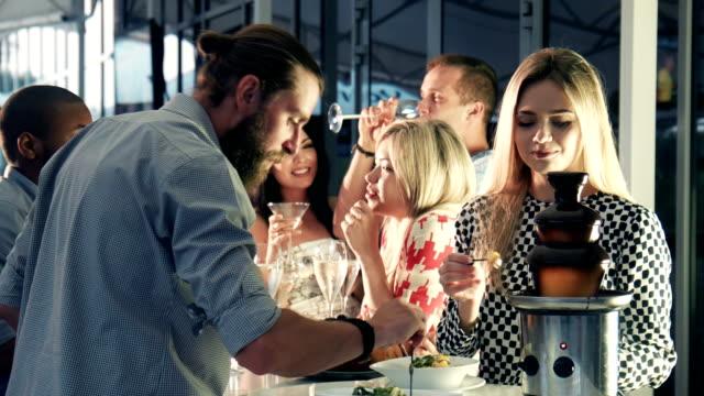 Friends dipping chocolate at fondue pot video