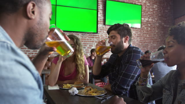 Friends Eating Out In Sports Bar With Screens Shot On R3D video