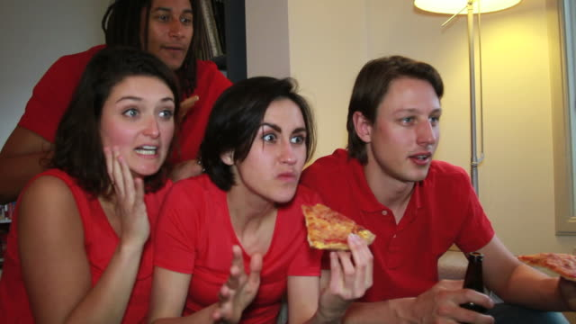 Friends eating pizza and watching television video