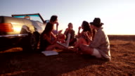 Friends eating pizza at sunset on an american road trip video