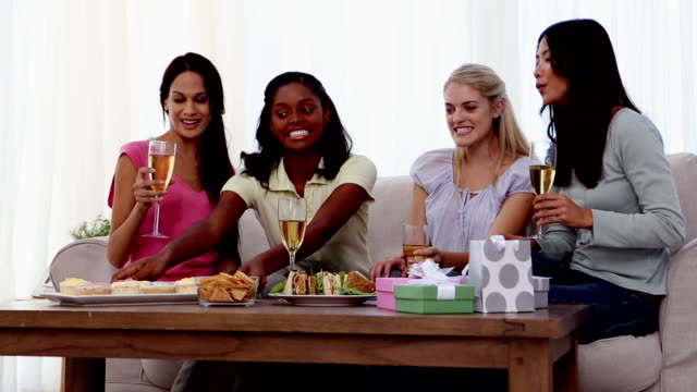 Friends eating snacks with flutes of champagne video