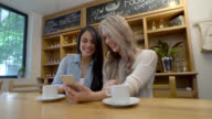 Friends enjoying a coffee while social networking on a smartphone video