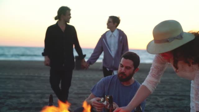 Friends enjoying s'mores at the beach. video