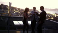 Friends hang out and have cocktails on a roof at sunset, with San Francisco in the background video