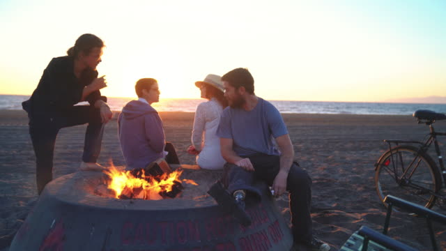 Friends hanging out on the beach with a fire video
