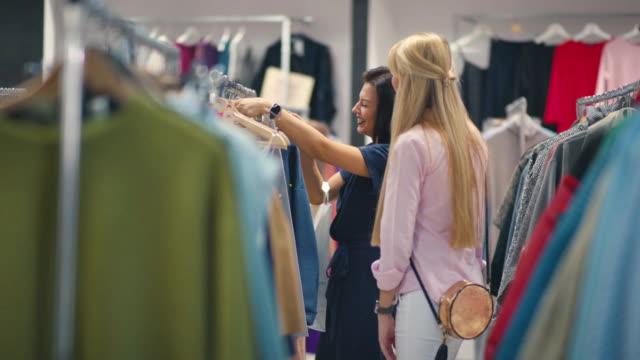 Friends happily shopping in clothing store. Clothing on hangers video