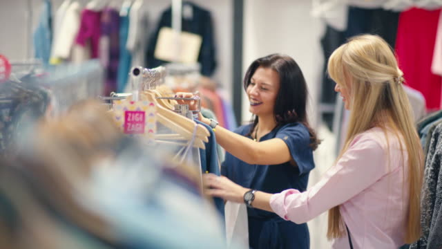 Friends happily shopping together in clothing store. Shopping video