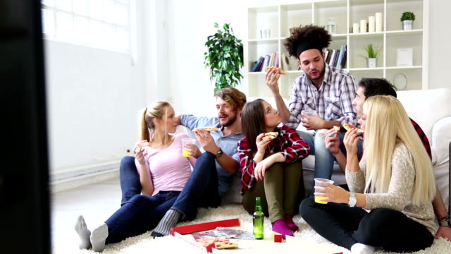 Friends have fun eating delicious pizza and drinking video