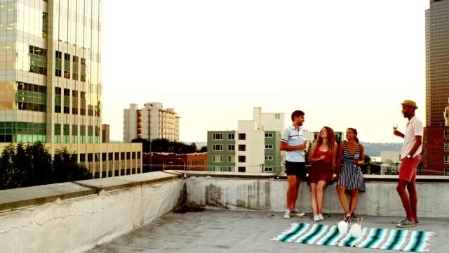 Friends having drinks on rooftop of building video