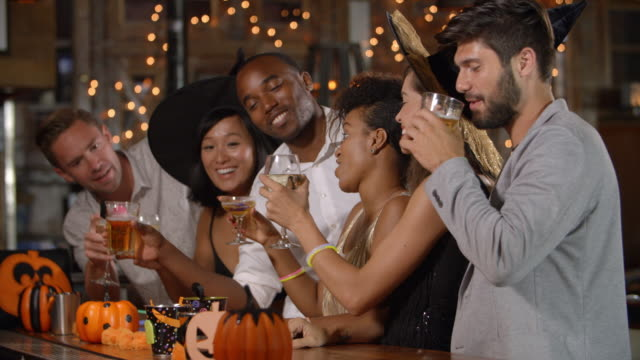 Friends having fun at a Halloween party in a bar video