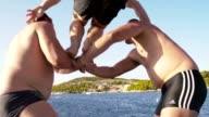 SLO MO Friends having fun jumping into the sea video