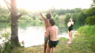 Friends having fun jumping off rope swing into river video