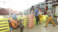Friends having fun on rooftop terrace, playing guitar, dancing and taking photos video