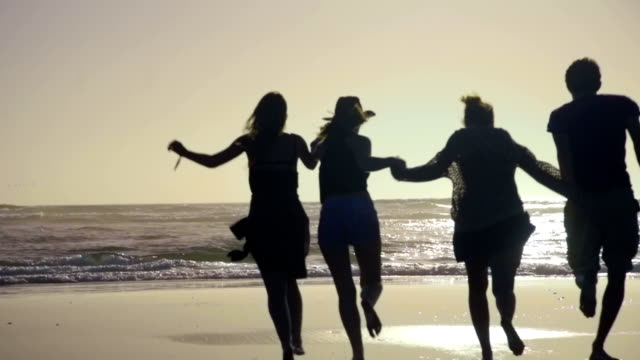 Friends hold hands and run toward the water video