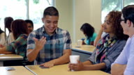 Friends in high school classroom laughing together while studying video