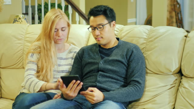 Friends - Korean man and Caucasian woman resting at home. Enjoy a tablet, a good time video