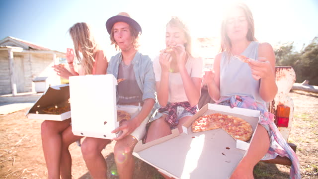 Friends laughing and enjoying pizza on a summer day video