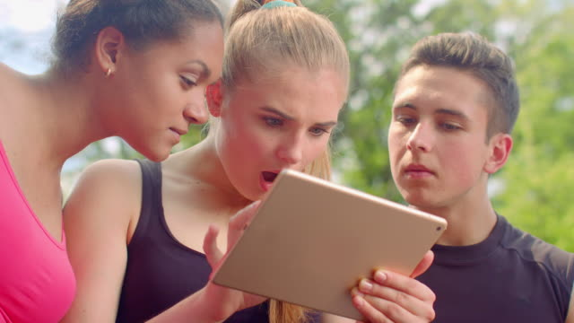 Friends looking tablet. Shocked faces. Surprised people. Young people tablet video