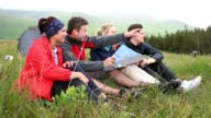 Friends on a camping trip laughing together and reading map video