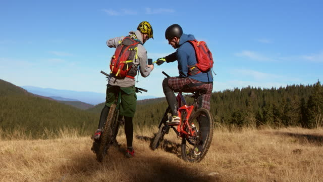 Friends on mountain bikes searching for the right trail with a phone video