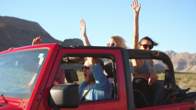 Friends On Road Trip Driving In Convertible Car Shot On R3D video