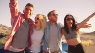 Friends On Road Trip Standing By Convertible Car Shot On R3D video