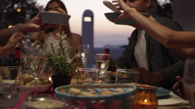 Friends passing food at dinner on a roof terrace, close up, shot on R3D video