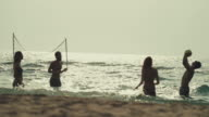 Friends play beach volley in the sea video