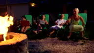 Friends relaxing on grassy lawn in backyard with drinks near stone fire pit video