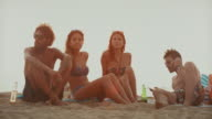 Friends relaxing together on the beach at sunset video