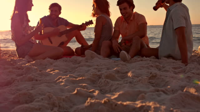 Friends sitting at the beach and playing guitar video