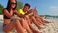 Friends sitting on the beach 4K video