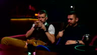 friends smoke from shisha pipei n the lounge caffee. Slow motion video