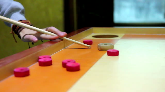 Friends spending evening leisure time, playing traditional oriental game carrom video