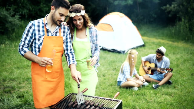 Friends spending time in nature and having barbecue video