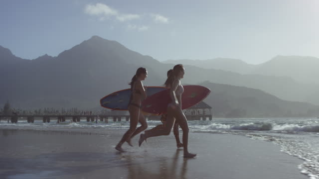 Friends surfing together on a tropical beach vacation to Hawaii video