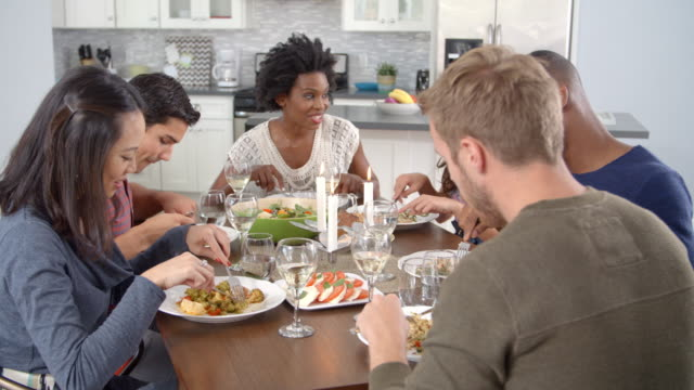 Friends talking and eating at a dinner table, shot on R3D video