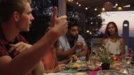 Friends talking at a dinner party on a roof terrace, Ibiza, shot on R3D video