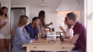 Friends talking over drinks and snacks in kitchen, Ibiza, shot on R3D video