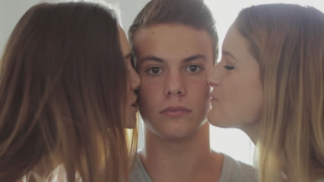 Friends together at home: teasing a guy with a kiss video