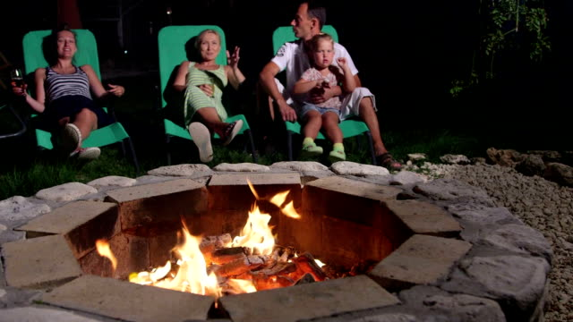 Friends with drinks lying on patio loungers around flaming fire pit talking video