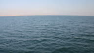 From shipbow over water going towards distant shoreline video