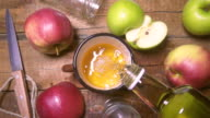 From the bottle pours fresh apple juice in glass. Rustic style Slow motion video
