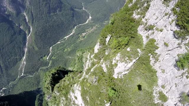 POV from wingsuit flier descending along mountain ridges video