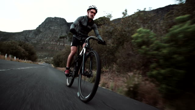 Front low angleshot of cyclist racing along mountain road video