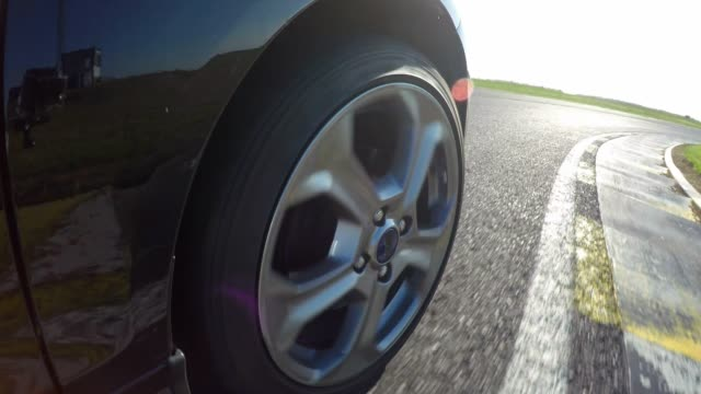 Front right wheel of a race car while racing video