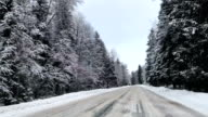 Front view from car mounted camera when vehicle driving winter snowy forest road video