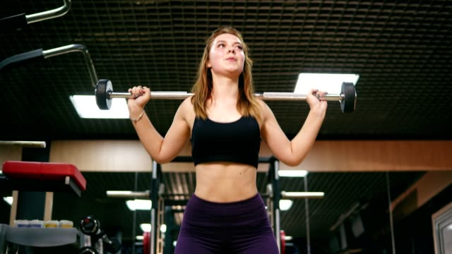 Front view of a young woman in short top and leggins in the gym doing squats with a barbell, improving the muscles of the buttocks and legs. Shot in 4k video