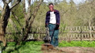 Front view of the man cultivating the ground with the garden cultivator video