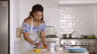 Front view of woman chopping and cooking ingredients at home, shot on R3D video